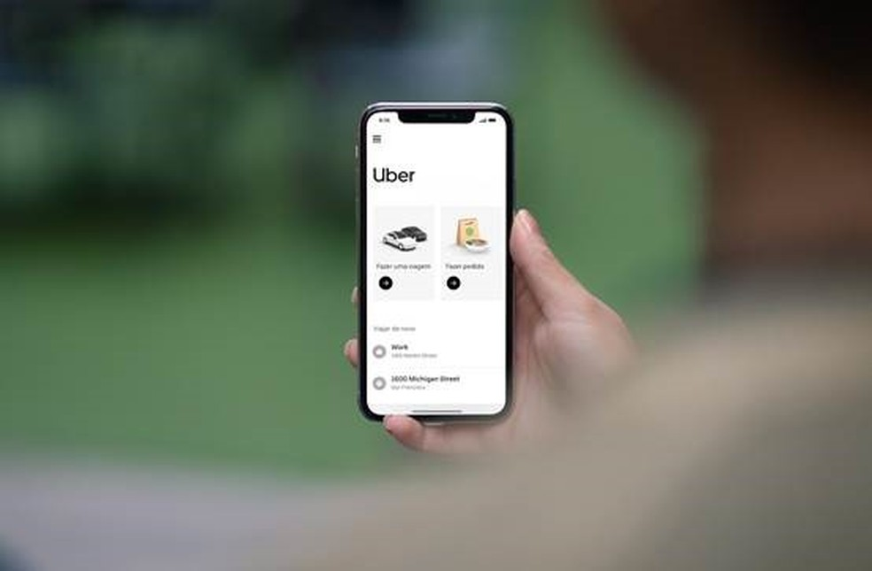 A imagem mostra uma mão segurando o celular no aplicativo do uber. Foto para ilustrar o texto  CNH para Uber o que é preciso para se tornar um motorista de aplicativo