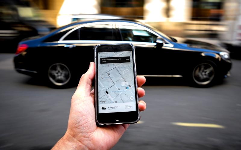 A foto mostrar uma mão segurando um celelular com o aplicativo do uber aberto. A foto ilustra o texto CNH para Uber o que é preciso para se tornar um motorista de aplicativo