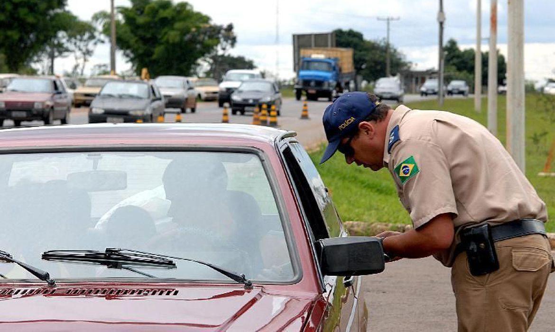 A foto mostra um policial conversando com o motorista de carro. Ela ilustra o texto Pauta_ Descubra para onde vai o dinheiro das multas de trânsito que você paga
