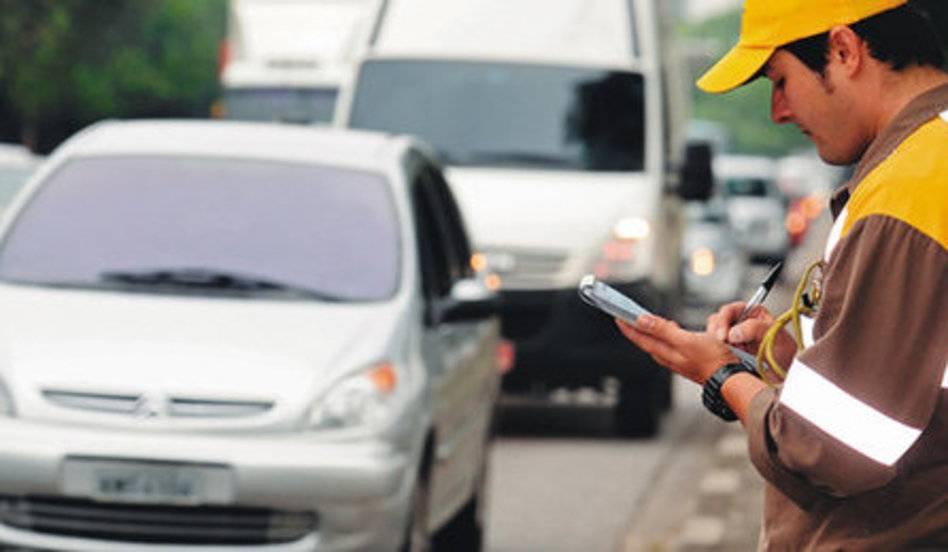 A foto mostra uma pessoa no trânsito realizando anotações. Ela ilustra o texto Descubra para onde vai o dinheiro das multas  de trânsito que você paga