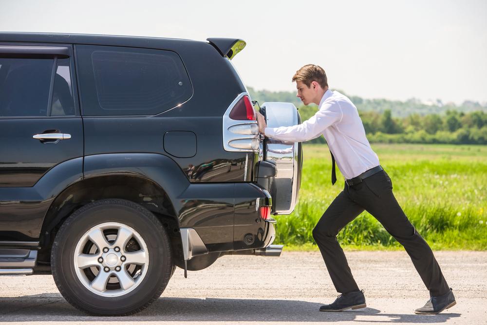 A foto mostra um homem empurrando um carro que está parado. Imagem para ilustrar o texto sobre multas curiosas