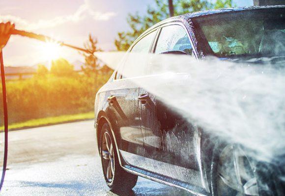 Foto mostrar um carro recebendo um jato de água; Imagem para ilustrar o texto sobre cuidados com o carro