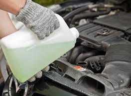 A foto mostra uma pessoa colocando água no motor. Imagem para ilustrar o texto sobre cuidados com o carro